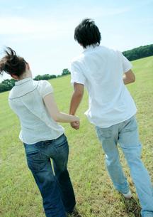 草原で手をつなぎ走るカップルの写真素材 [FYI04063850]