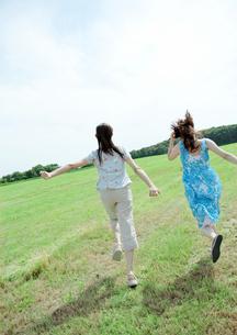 草原を駆ける2人の女性の写真素材 [FYI04063853]