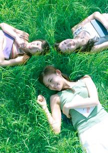 草原に寝転びくつろぐ3人の女性の写真素材 [FYI04063857]