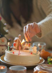 クリスマスケーキのキャンドルに火を灯す女性の写真素材 [FYI04063910]