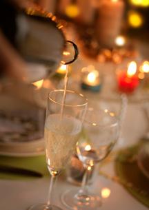 クリスマスキャンドルとグラスに注いだシャンパンの写真素材 [FYI04063917]