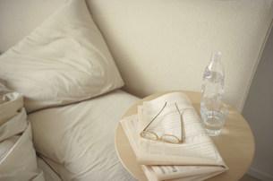 新聞と眼鏡を置いたサイドテーブルとベットの写真素材 [FYI04063926]