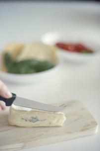 ナイフでチーズを切る手元の写真素材 [FYI04063929]