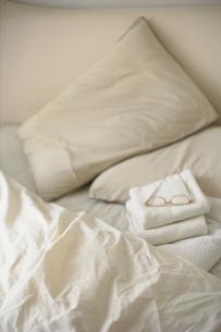 ベッドの上に重ねたタオルと眼鏡の写真素材 [FYI04063935]