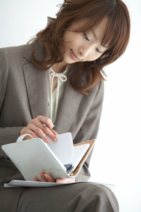 手帳を見る女性の手元の写真素材 [FYI04064961]