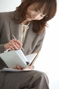 手帳を見る女性の手元の写真素材 [FYI04064963]