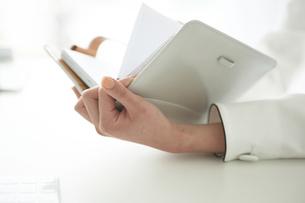 デスクで手帳を見る女性の写真素材 [FYI04064990]