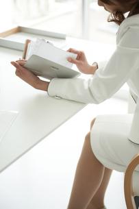 デスクで手帳を見る女性の写真素材 [FYI04064992]