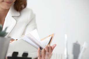 手帳を見る女性の手元の写真素材 [FYI04064998]