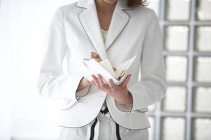 手帳を見る女性の手元の写真素材 [FYI04064999]