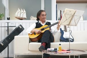 ソファに座り楽譜を見ながらギターを弾く男性の写真素材 [FYI04065422]