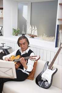 ソファに座り楽譜を見ながらギターを弾く男性の写真素材 [FYI04065424]