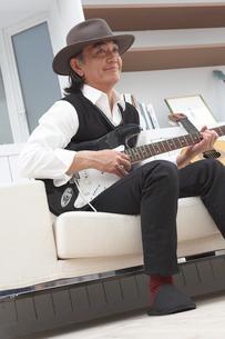 ソファに座り帽子を被ってギターを持つ男性の写真素材 [FYI04065427]