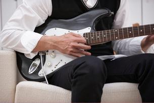 ソファに座りギターを弾く男性の手元の写真素材 [FYI04065430]