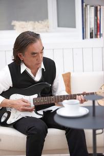 ソファに座りギターを弾く男性の写真素材 [FYI04065432]