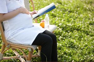 公園で雑誌を読む妊婦の写真素材 [FYI04065525]