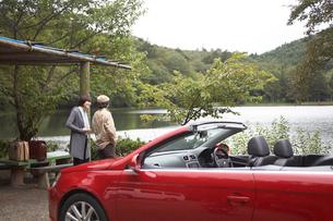 湖畔の赤いオープンカーと男女の写真素材 [FYI04065557]
