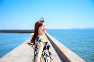港の防波堤を歩く海のリゾートへ旅する女性の写真素材 [FYI04065611]