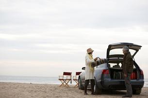車から荷物をおろす男性と女性の写真素材 [FYI04065660]