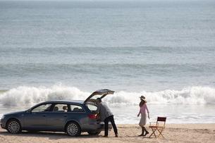 波打ち際の男女と車の写真素材 [FYI04065668]