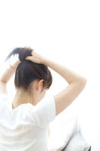 髪の毛を束ねる女性の写真素材 [FYI04065715]