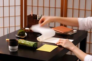 机の上で便箋をめくる女性の手元の写真素材 [FYI04066096]