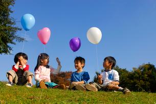 風船を持ち草の上に座る子供4人(男女)の写真素材 [FYI04066308]