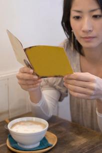歌詞カードを読む女性の写真素材 [FYI04066324]