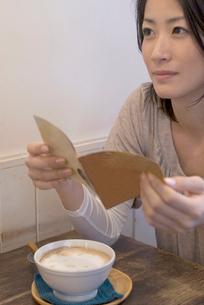 歌詞カードを読む女性の写真素材 [FYI04066325]