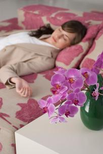 胡蝶蘭とソファで眠る女性の写真素材 [FYI04066373]
