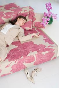 ソファで眠る女性と胡蝶蘭の写真素材 [FYI04066379]