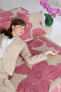ソファで眠る女性と胡蝶蘭の写真素材 [FYI04066381]
