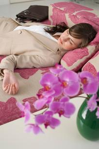 胡蝶蘭とソファで眠る女性の写真素材 [FYI04066382]