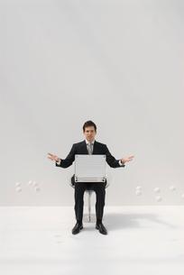 椅子に座るビジネスマンと白いボールの写真素材 [FYI04066387]