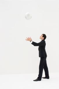白い地球儀を投げるビジネスマンの写真素材 [FYI04066401]