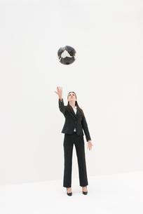 黒い地球儀を投げる女性の写真素材 [FYI04066402]