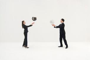 白と黒の地球儀を投げるビジネスマンと女性の写真素材 [FYI04066403]