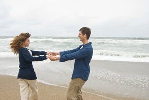 砂浜で戯れる男女の写真素材 [FYI04066423]