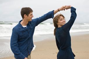 砂浜で戯れる男女の写真素材 [FYI04066424]