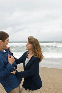 砂浜で戯れる男女の写真素材 [FYI04066428]