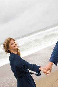 砂浜で戯れる男女の写真素材 [FYI04066437]