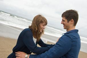 砂浜で戯れる男女の写真素材 [FYI04066444]