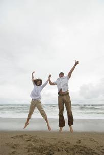 砂浜でバンザイしてジャンプする男女の写真素材 [FYI04066452]