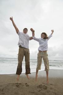 砂浜でバンザイしてジャンプする男女の写真素材 [FYI04066455]