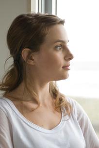 部屋の窓辺に立って外を見ている女性の写真素材 [FYI04066537]