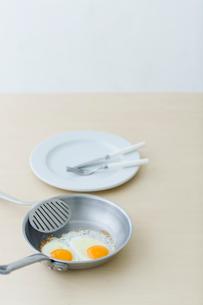 目玉焼きと皿とフライパンとカトラリーの写真素材 [FYI04066692]