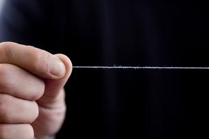 糸をひっばる男性の手元の写真素材 [FYI04066750]