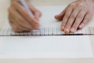 定規で紙に線を引く女性の手元の写真素材 [FYI04066754]