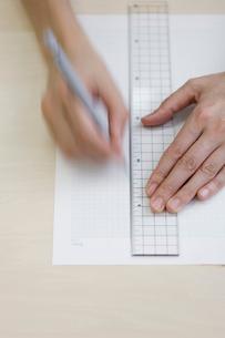 定規で紙に線を引く女性の手元の写真素材 [FYI04066762]