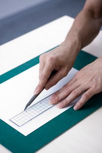 カッターで紙を切る男性の手元の写真素材 [FYI04066763]